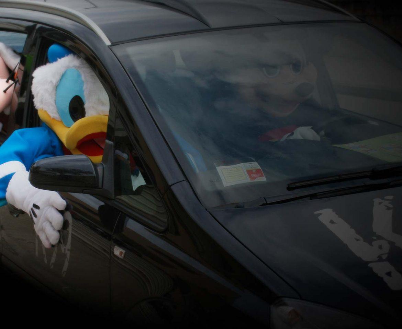 Marketing non convenzionale, paperino, topolino e pippo che guidano un automobile